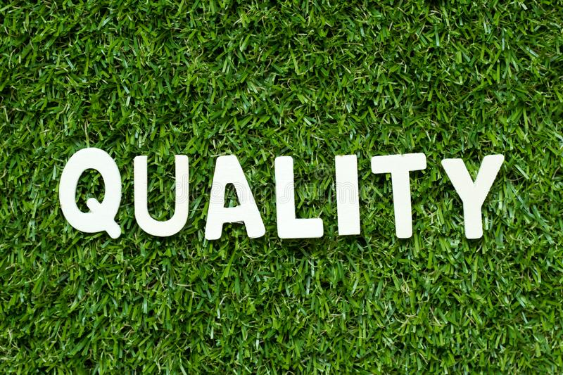 Alphabet in word quality on artificial green grass background. Alphabet letter in word quality on artificial green grass background stock image