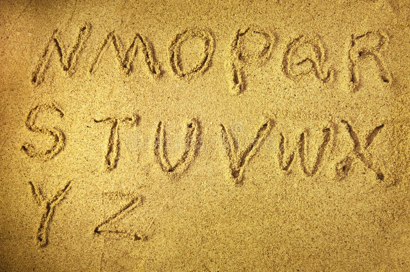 Alphabet letters. Handwritten in sand on beach royalty free stock photography