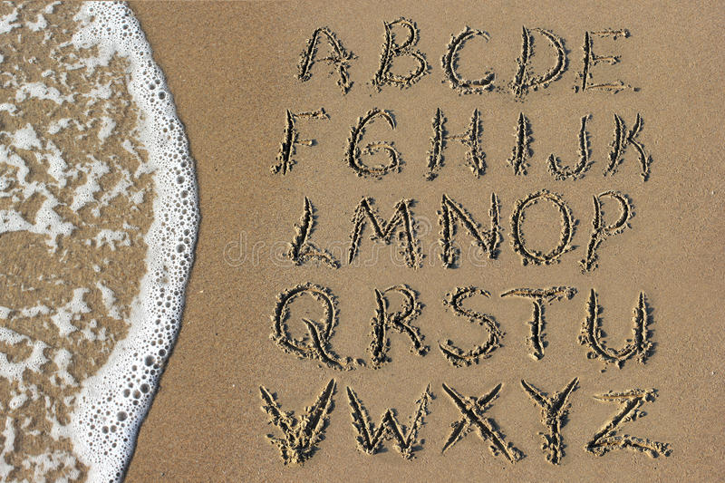 Alphabet letters handwritten in sand on beach. Go to the beach will be prepared for use in writing the alphabet photo stock photo