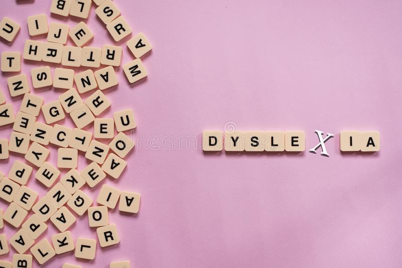 Dyslexia concept - alphabet letters on pink background. Alphabet letters on pink background.block letters are placed globally on a pink background.education stock photography