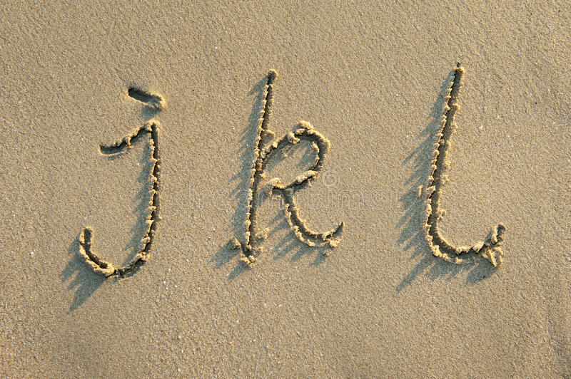 Alphabet letters in sand on beach. Alphabet letters handwritten in sand on beach royalty free stock photos