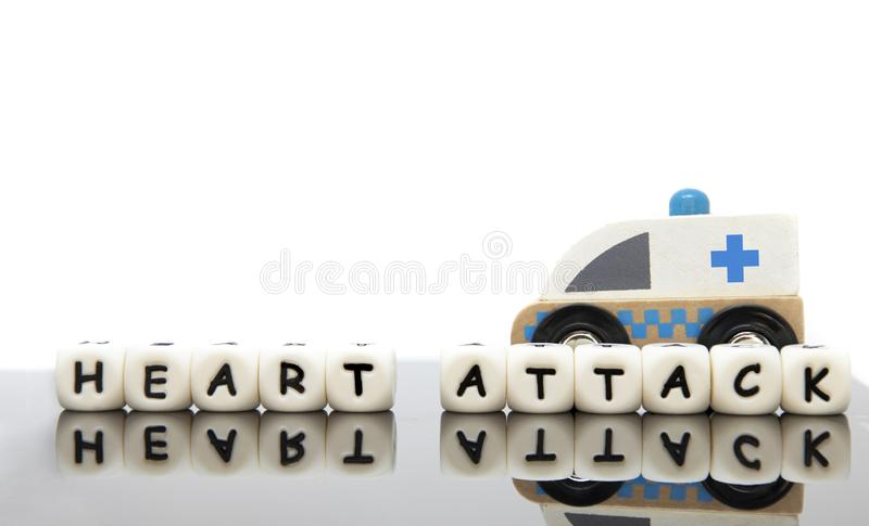 Alphabet letters spelling the word heart attack and a toy ambulance. Alphabet letters spelling the word heart attack and a wooden toy ambulance. White background royalty free stock photos