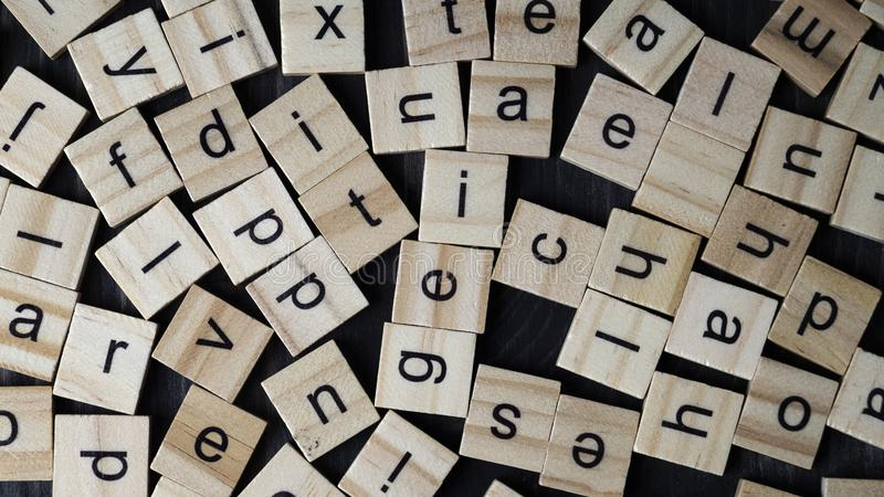 Alphabet letters on wooden scrabble pieces. From above royalty free stock image