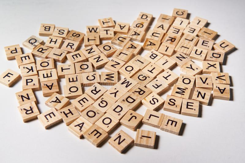 Alphabet letters on wooden scrabble pieces scattered stock photos