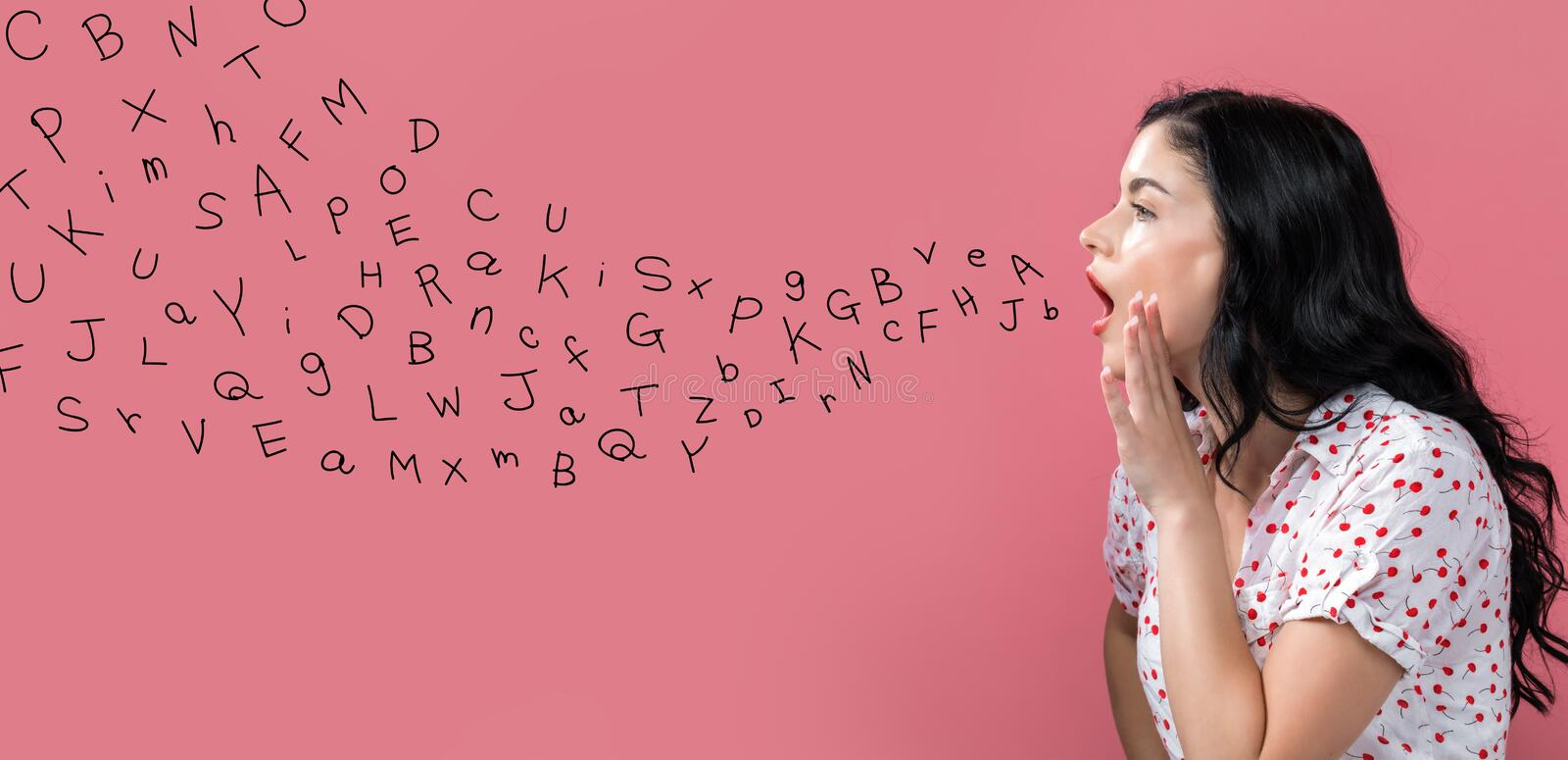 Alphabet letters with young woman speaking royalty free stock images