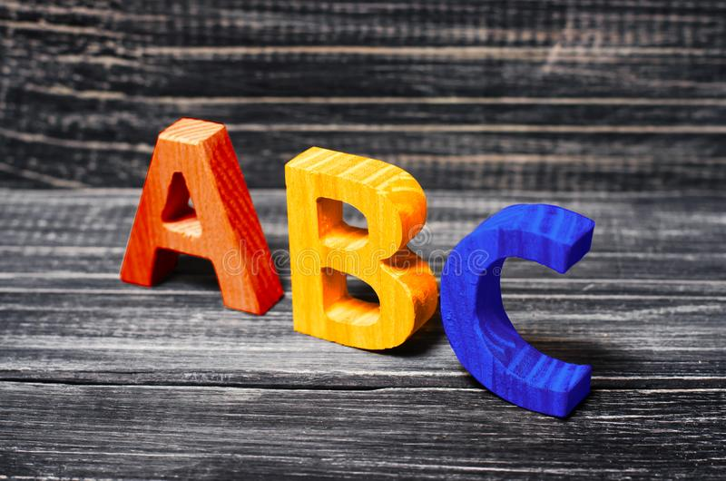 Alphabet made of wood on the background of a board, ebony. Concept of education, English. English letters, retro. stock image
