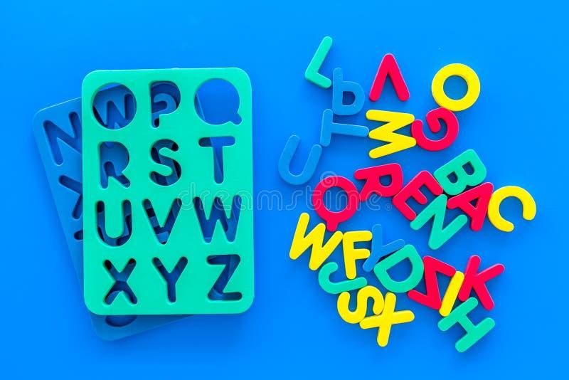 Alphabet pour le concept d'enfants Lettres anglaises dans le désordre près du pochoir sur la vue supérieure de fond bleu photos stock