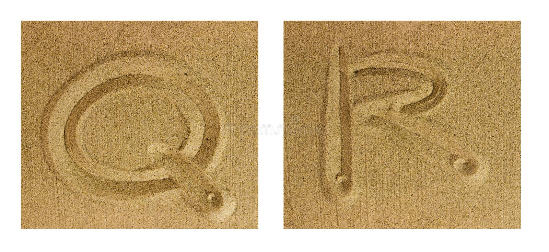 Alphabet Q-R on sand. Alphabet letters hand written in sand on beach stock photography