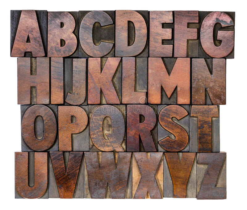 Alphabet in vintage wood type. English alphabet in letterpress wood type printing blocks, stained by color inks stock photos