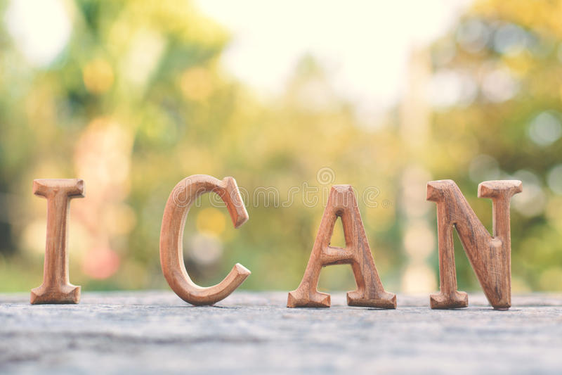 Alphabet wood `I can` word. On tree bokeh background royalty free stock image