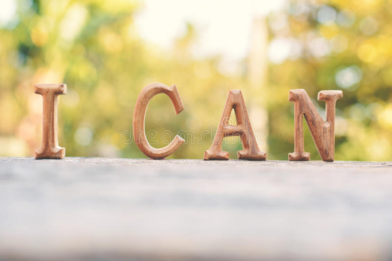 Alphabet wood. `I can` word on tree bokeh background stock photography