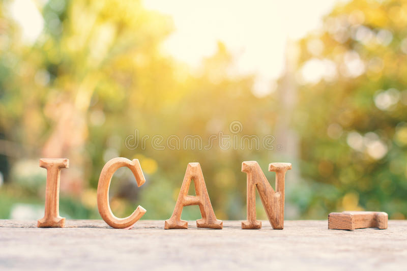 Alphabet wood. `I can` word on tree bokeh background royalty free stock image