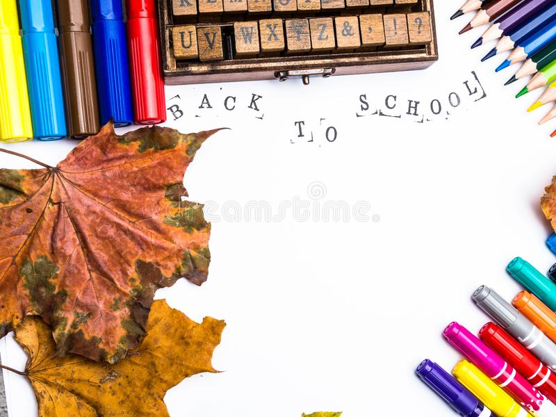Alphabet in wooden box, colorful pencils and markers, dry autumn leaves isolated on white background, Hello school, 1st September royalty free stock photography