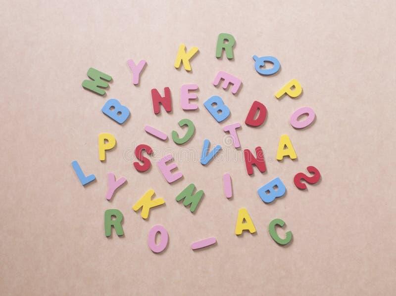 Alphabets colorés sur le papier brun photos stock