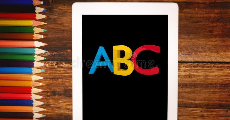 Alphabets sur la tablette par des crayons de couleur illustration de vecteur