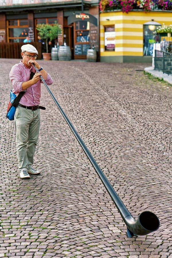 Alphorn gracz zabawia ludzi przy restauracją w Ascona zdjęcie royalty free