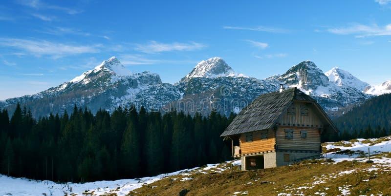 Alpiene berghut met sneeuwpieken royalty-vrije stock afbeelding