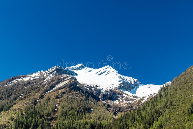 Alpiene die berg met piek door sneeuw wordt behandeld stock foto's