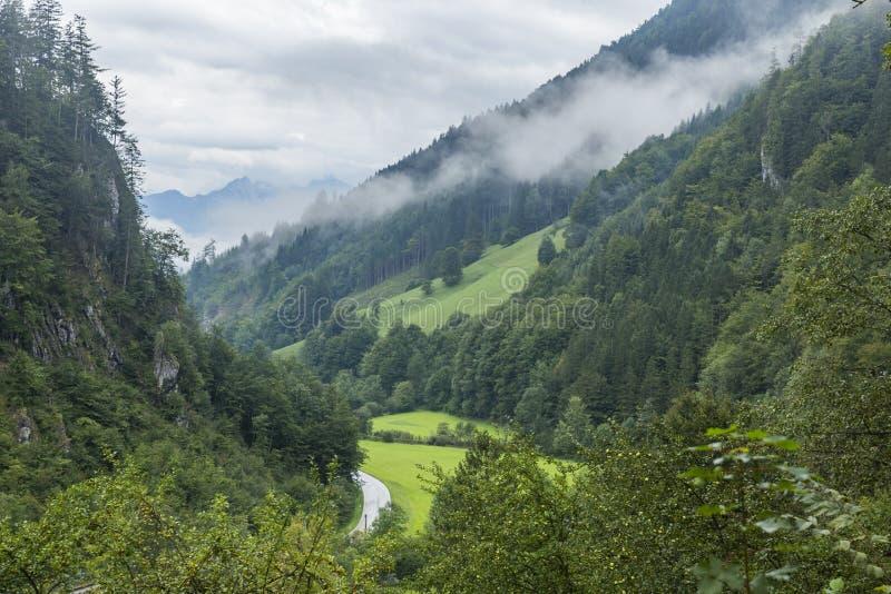 Alpiene vallei na regen met de wolken die met de weg opheffen die het kruisen royalty-vrije stock afbeeldingen