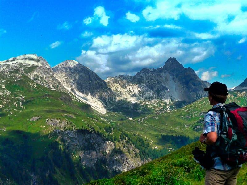 _ alpin En fotvandrare ser in i avståndet En fotvandrare med en ryggsäck ser vaggar royaltyfria bilder