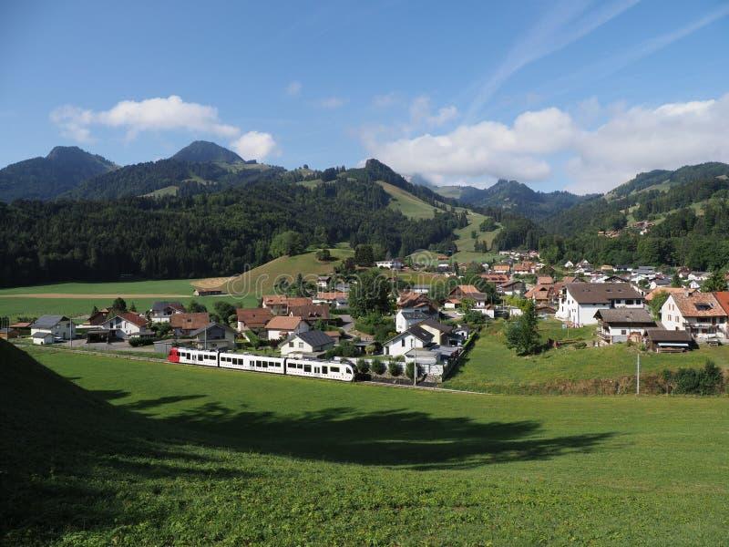 Alpin panorama med hus och det moderna drevet på den européGruyeres staden i Schweiz på Augusti arkivbilder