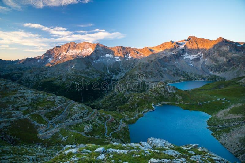 Alpin sjö för hög höjd, fördämningar och vattenhandfat i idylliskt land med majestätiska maxima för stenigt berg som glöder på so arkivfoton