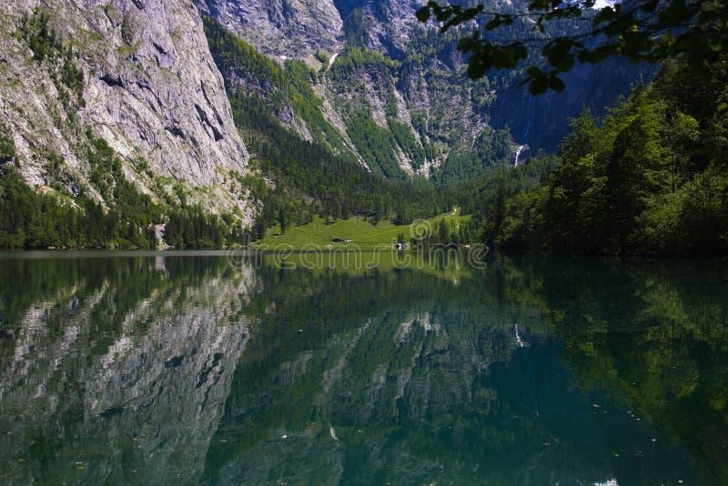 Alpina fjällängar för sjö på våren Sikt av kusten från kojan av den alpina sjön Reflexion av berg i det kristallklart royaltyfri bild