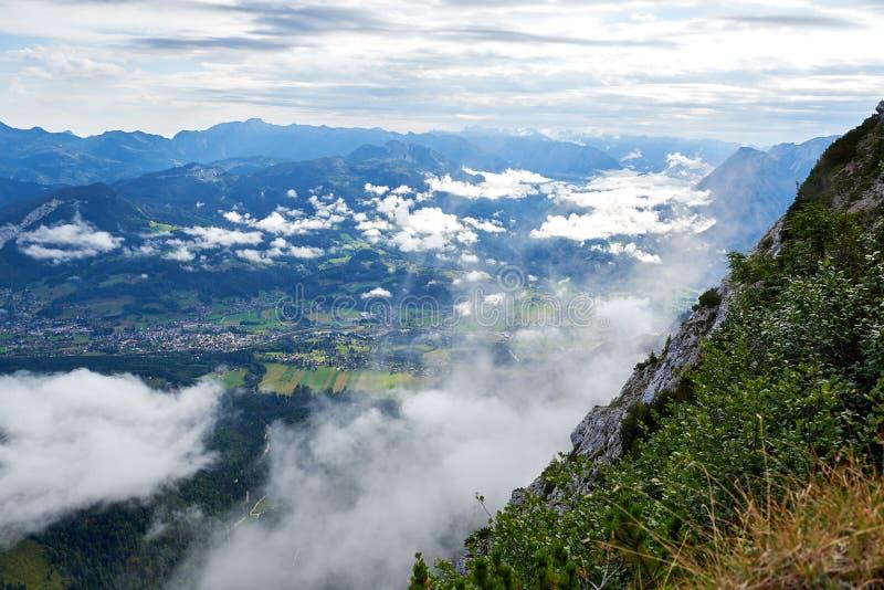 Alpina gräsplanfält och traditionell trähussikt av den dåliga Goisern byn på den soliga dagen för sommar Många moln royaltyfria bilder