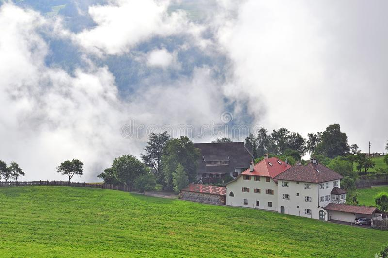 Alpina hus i moln arkivbild
