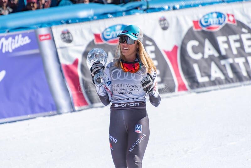 Alpina total- FIS skidar toppna Gs vinnare som USA Mikaela Shiffrin firar, som hon rymmer kristalljordklottrofén under podiumcen royaltyfria bilder