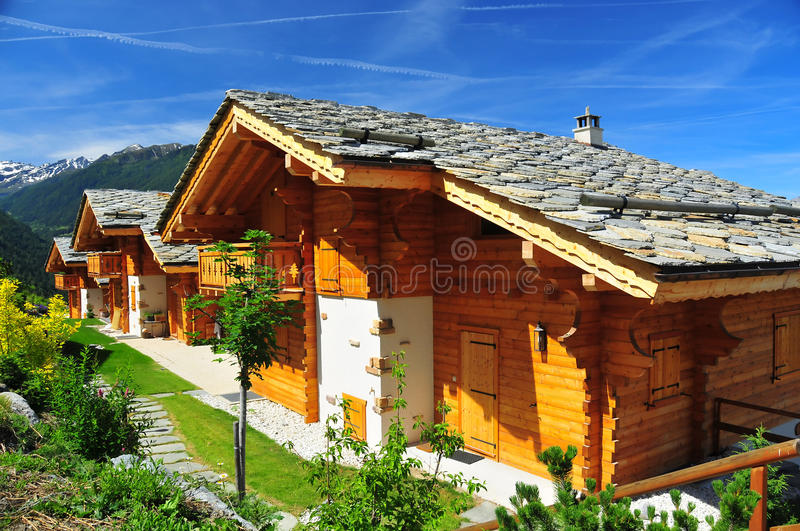 Alpine chalets. 3 alpine chalets in the sunshine, with mountains in the background. With traditional rectangular section wood walls and stone roofs with snow stock photography