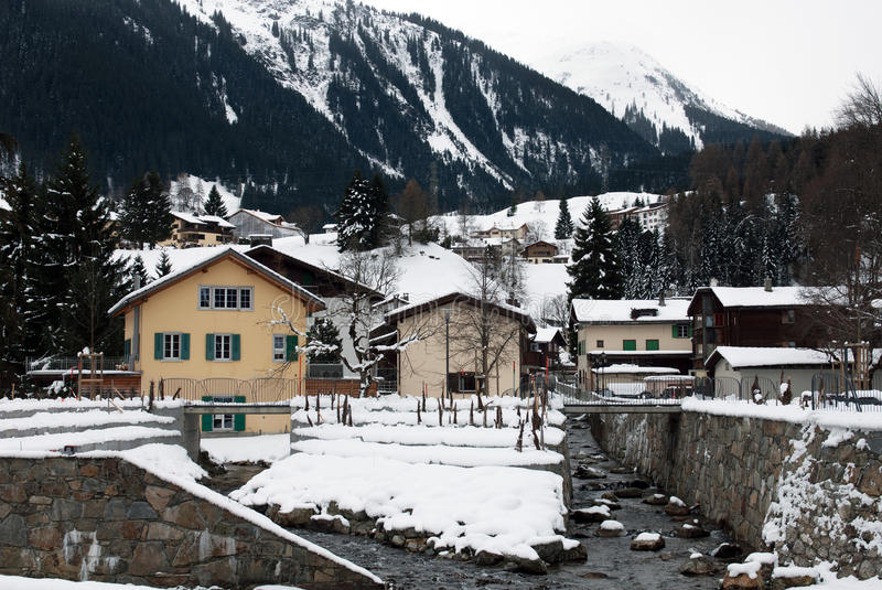 Alpine Chalets, Klosters, Switzerland. Houses adjacent to a mountain stream, near Klosters, in Switzerland royalty free stock photo