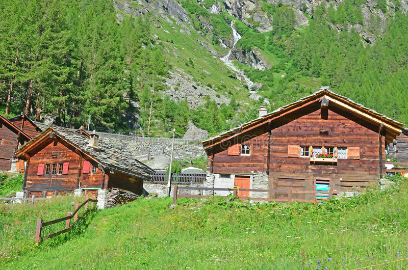 Alpine Chalets. In their flower filled meadows with a stream and mountainside in the background stock image