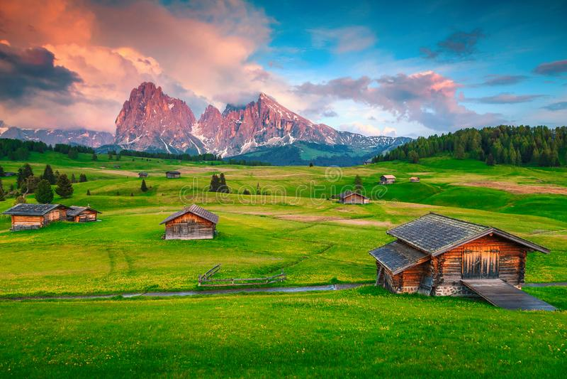 Alpine grüne Felder und hölzerne Chalets bei Sonnenuntergang, Dolomit, Italien stockbild
