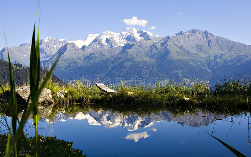 Alpine lake. Breathtaking scene of Alpine lake with relax chair. Snowy mountains in background royalty free stock image