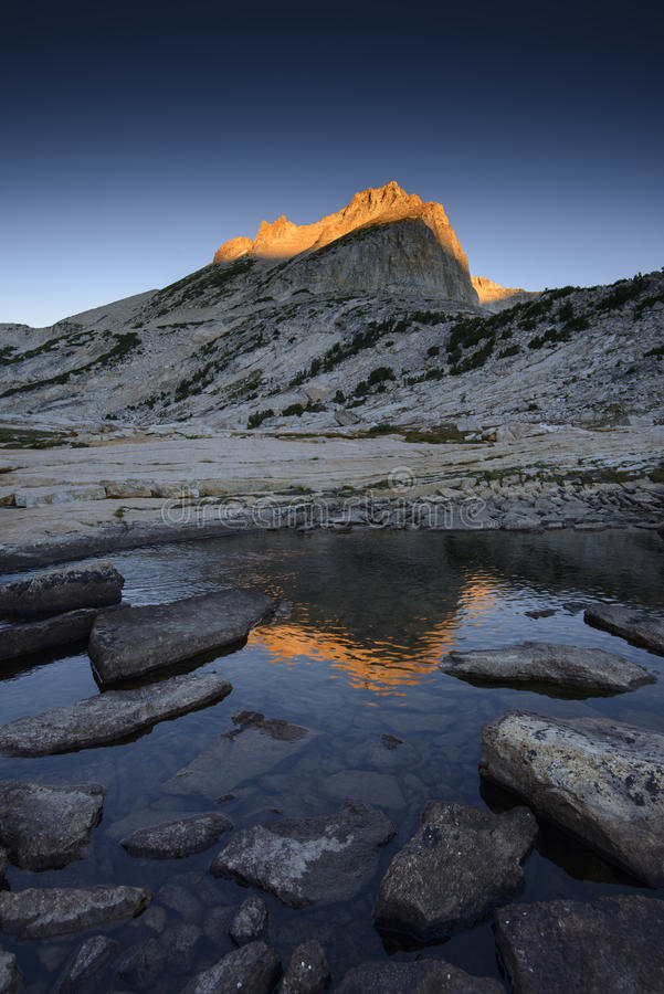 Alpine lake and Noth Peak of Mount Conness at sunrise stock image