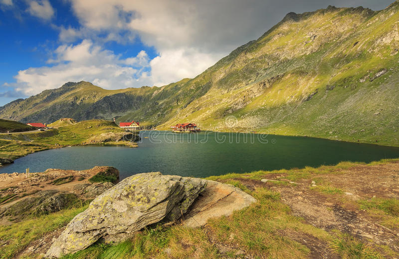 Alpine lake and restaurant on a lake,Balea lake,Fagaras mountains,Carpathians,Romania. Wonderful mountain lake and cloudy sky,Balea lake,Fagaras mountains stock photography