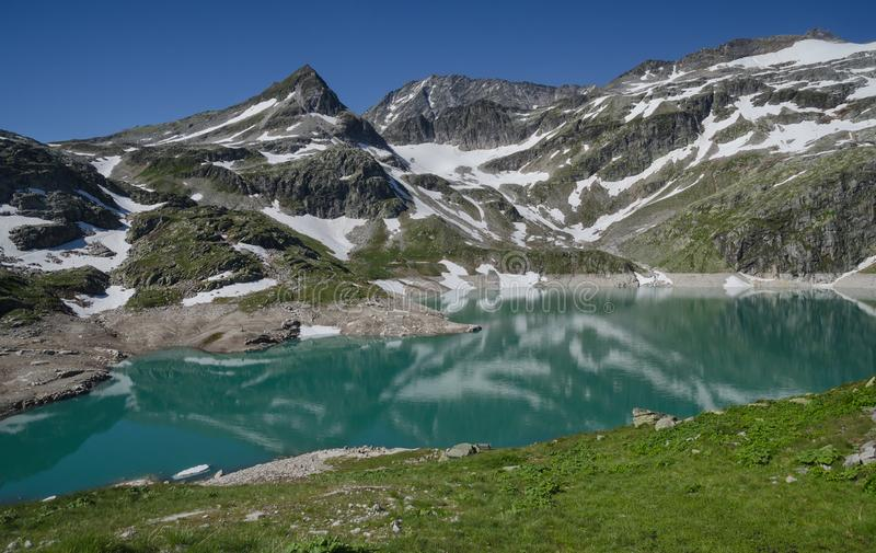 Alpine lake and snowy peaks in summer. Alpine lake with snowy peaks above Enzingenboden, Hohe Tauern NP, Austria stock photography
