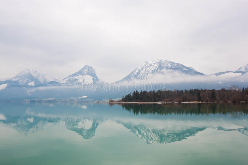 Alpine lake Wolfgangsee, Austria. Wolfgangsee, a beautiful lake in austrian alps. Winter, cloudy sky, mountains reflecting in water. Austria royalty free stock images
