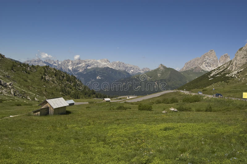 Alpine landscape. Grass and small house among the dolomites chain, italian alps stock photo