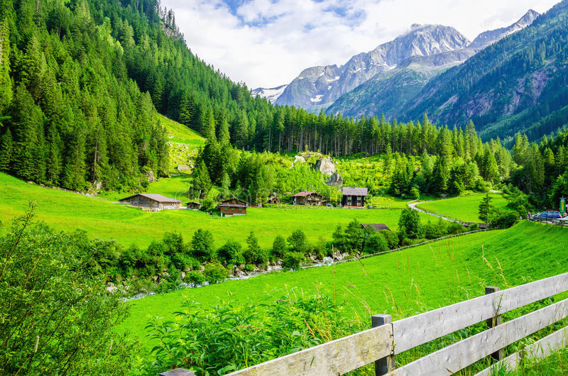 Alpine landscape with green meadows, Alps, Austria. Beautiful alpine landscape with green meadows, alpine cottages and mountain peaks, Zillertal Alps, Austria royalty free stock photos