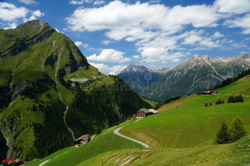 Alpine landscape with scattered houses on a hillside. View into the Kaiserbach valley from Kaisers. Some houses are scattered on the hillside The background is a stock photography
