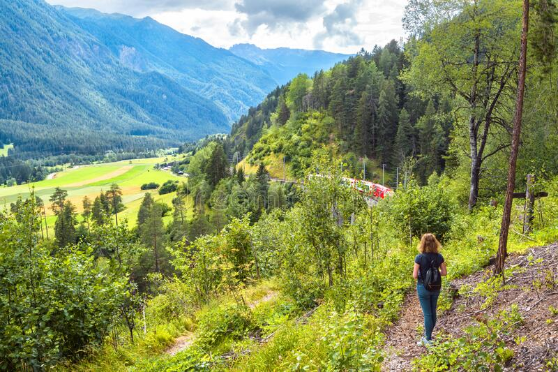 Alpine landscape in summer, Filisur, Switzerland. Young woman looks at red train of Bernina Express in forest. Adult girl travels royalty free stock photography