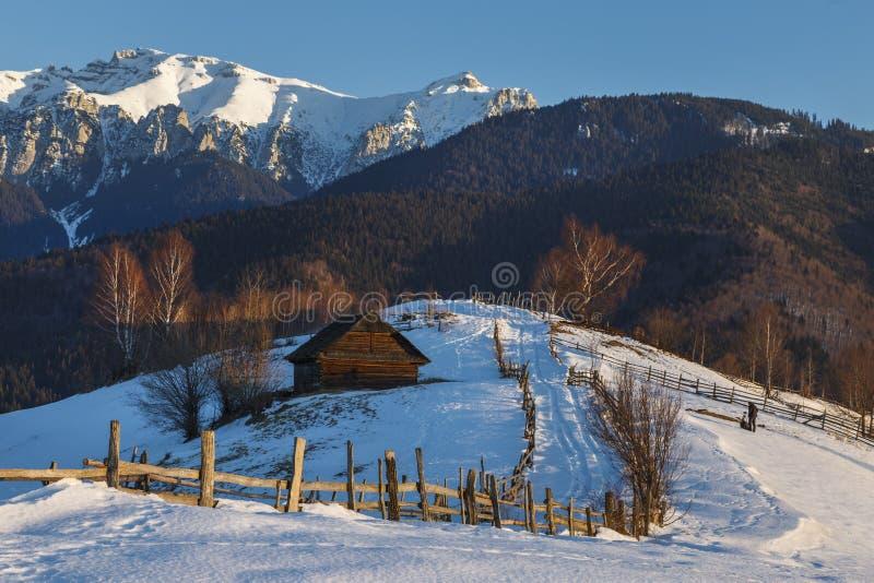 Alpine Landschaft mit rustikalem hölzernem Häuschen und Schnee bedeckte Kante der Bucegi-Berge im Sonnenunterganglicht in einer K stockbilder