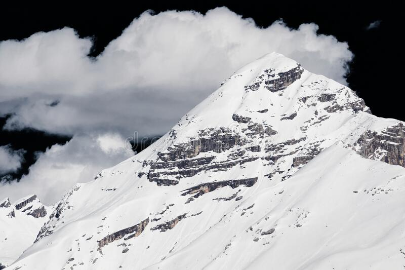 Alpine mountain under a dark sky. Black sky on snowy mountain of Alps with a white cloud around royalty free stock image