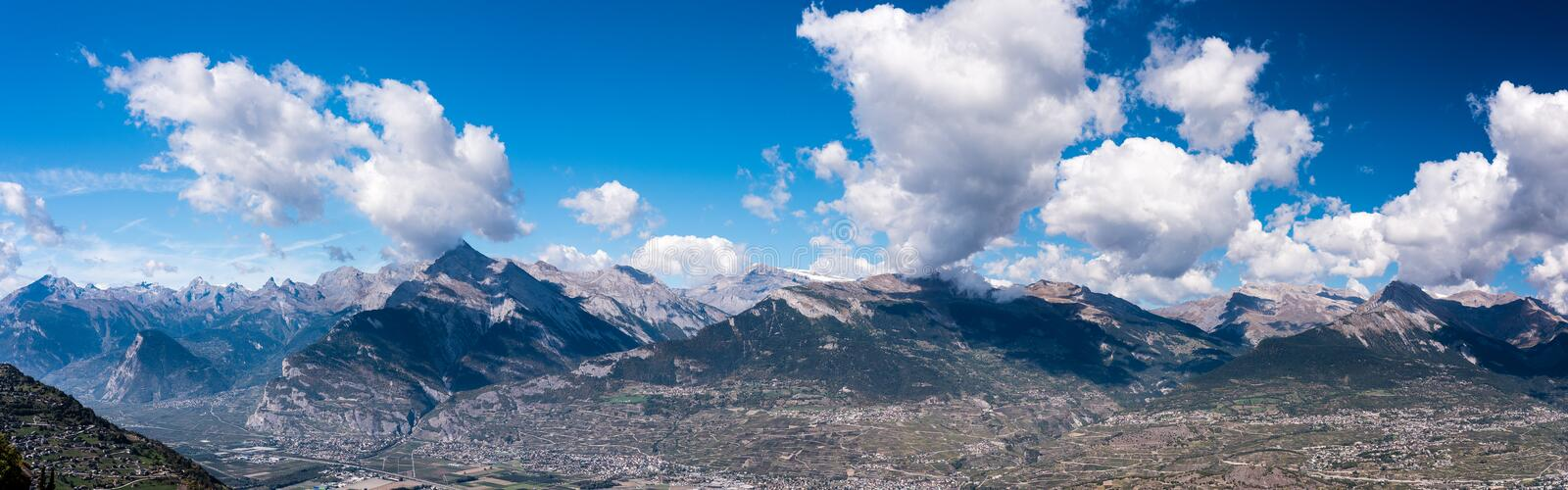 Alpine mountains with shadows of clouds, large panorama royalty free stock photo