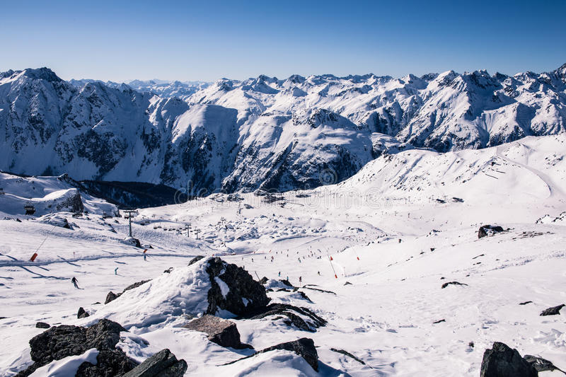 Overlooking Ischgl Ski Resort. Alpine panorama showing snow covered mountains and a clear blue sky royalty free stock image