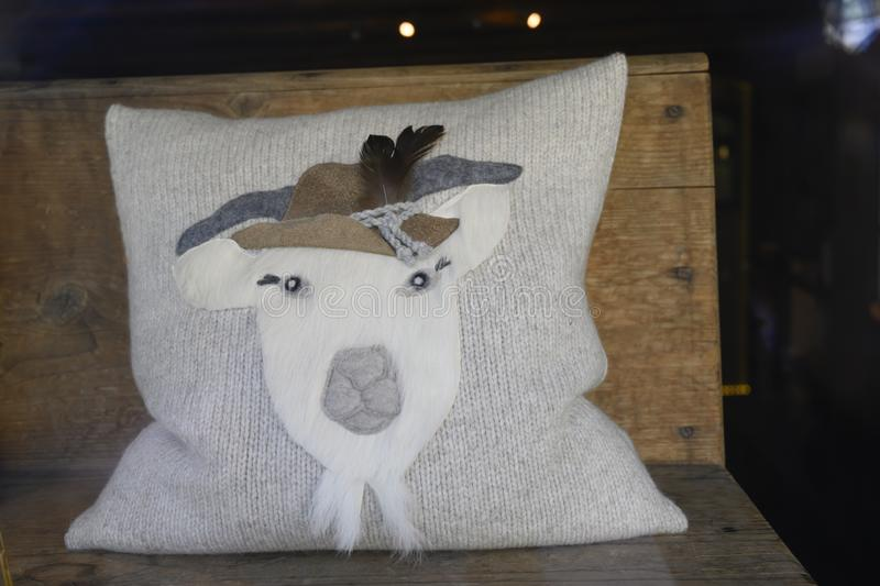 Alpine Pillow, Goat with traditional hat on knitted grey Pillow in Switzerland royalty free stock images