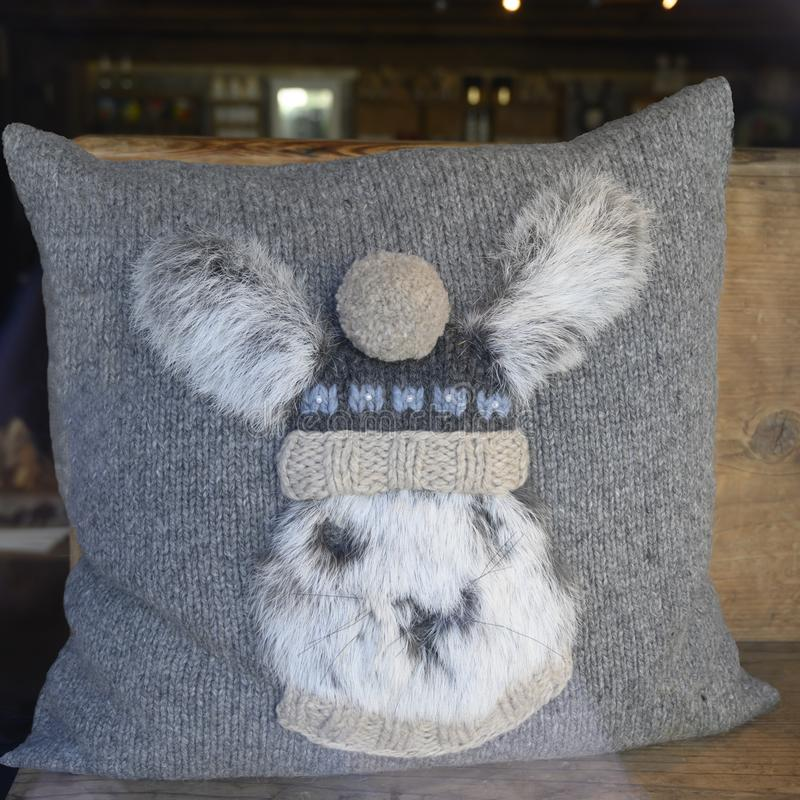 Alpine Pillow, rabbit with traditional bobble hat on knitted grey Pillow in Switzerland stock image