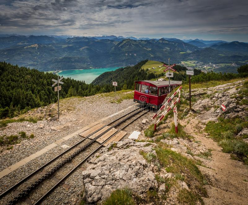 Alpine rack railway track to Schafberg, where steam train takes tourists on a mountain peak in the Austrian Alps near Salzburg. Passing pedestrian crossing on stock photography